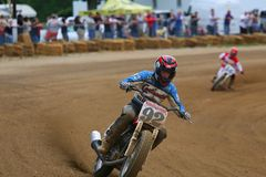Dirt bike racing event. Biker leans his motorcycle as he rides the sharp turn of the dirt track at the vintage motorcycle racing event on the dirt oval flat Royalty Free Stock Images
