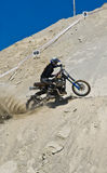 Dirt bike rider. Going up a sandy hill Stock Image