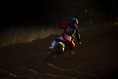 Dirt Bike Rider Sunset. Dirt bike rider going into the sun stock photo