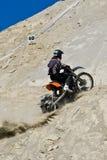Dirt Biker. Dirt bike rider climbing a sandy hill Royalty Free Stock Photos