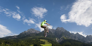 Dirt biker jumps high up in the air with mountains Stock Photo