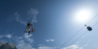 Dirt biker makes stunt with mountain and ropeway Stock Photo