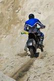 Dirt biker riding up hill stock photos