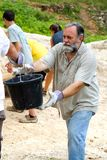 Dirt Bucket Brigade. Man helps pass along a bucket of dirt to a fellow missionary on a trip to build a church in Jamaica royalty free stock photo