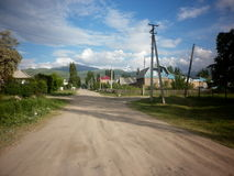 Dirt Country Road. This is a dirt country road with stunning clouds in the sky as shadows lengthen across the track. Taken in Karakol, Kyrgyzstan Royalty Free Stock Image