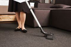 Dirt have no chances to survive. Cropped portrait of woman in maid uniform cleaning floor with vacuum cleaner, working. In house of her employer, wiping all Royalty Free Stock Photo