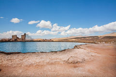 Dirt landscape with mountain lake under white clouds in Middle East. Dirt landscape with mountain lake under white clouds with the ruins of an ancient stone city Royalty Free Stock Photos