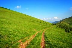 Dirt long road among green hills Royalty Free Stock Photo