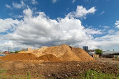 Dirt mound on a background of blue sky with white clouds.  royalty free stock photo