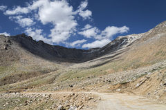 Dirt mountain road bend with yaks feediing beside royalty free stock image