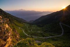 Dirt mountain road leading to high mountain pass in Italy Colle delle Finestre. Expasive view at sunset, colorful dramatic sky, Stock Image