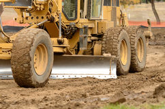 Dirt Movement. Large surface grader tractor works at moving soil and rock for a new commercial housing development Stock Photo