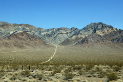 Dirt path leading to bare mountain, Nevada Stock Image