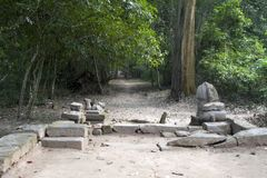 Dirt path with lion guardians at the east entrance to the 12th century Preah Khan temple complex royalty free stock image