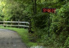 Dirt path in the woods with clock for timing a race. A clock is nine minutes into a 10K running race being held in the woods on a dirt trail souranded by trees royalty free stock images