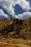 Dirt Pile. A pile of dirt at a construction site with blue sky and clouds Stock Photos