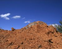 Dirt piled high arrow shaped c. A pile of dirt and rocks with clouds forming an arrow above it. could be concept for building royalty free stock photos