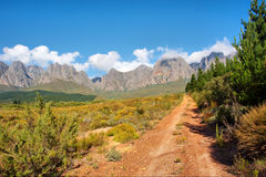 Dirt red road towards majestic mountains Royalty Free Stock Images