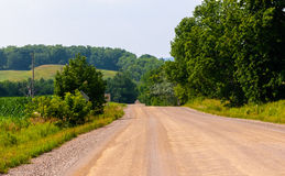 Dirt road against hills and trees Stock Photo