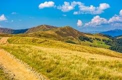 Dirt road through alpine hills of mountain ridge Royalty Free Stock Image