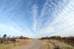 Dirt Road with Altocumulus Clouds Royalty Free Stock Photography