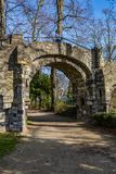 Dirt road and the arch of an old stone bridge with a woman on it, a dirt road in the Proosdij park. A wonderful and sunny day in Meerssen south Limburg in the royalty free stock image