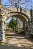 Dirt road and the arch of an old stone bridge with a woman in it taking a picture,. A dirt road in the Proosdij park, a wonderful and sunny day in Meerssen stock image