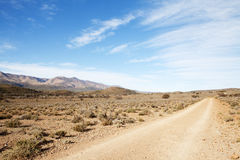 Dirt road in arid region leading away from viewer Stock Photos