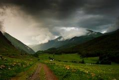 Dirt road in Caucasus mountains. Before the rain Stock Images