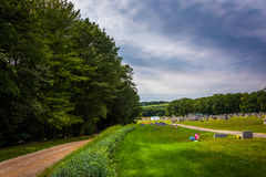 Dirt road and cemetery in rural York County, Pennsylvania. Royalty Free Stock Images