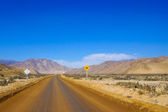 Dirt road in Chile. A long and empty road in the desert in northern Chile Stock Image