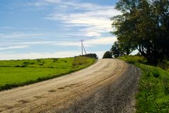 Dirt road in countryside on blue sky Stock Photo