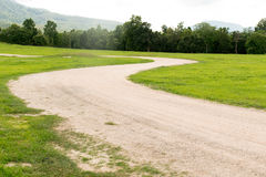 Dirt road curve on green grass park Royalty Free Stock Photography