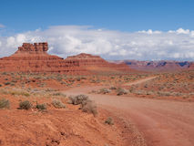 Dirt road into desert landscape. This dirt road travels through a desert landscape filled with dramatic chiffs and rock formations in the Valley of the Gods in Royalty Free Stock Photography