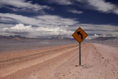 Dirt road into endlessness of Atacama desert -  yellow traffic sign showing left direction, Chile royalty free stock photo