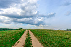 Dirt road in a field. Against a blue sky Stock Images