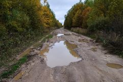 Dirt road with big puddles in autumn Stock Images