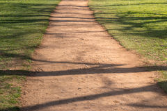Dirt Road between Grass. With Woods' shadow Royalty Free Stock Images