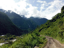 Dirt Road in Green Lower Himalayas. A dirt road in the lower green Himalayas of the Annapurna region in Nepal during monsoon Royalty Free Stock Photo