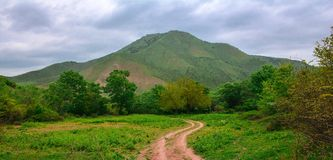 Dirt road on green mountain landscape Royalty Free Stock Image