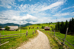 Dirt road in a green village under blue sky and white clouds Stock Photos