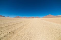 Dirt road at high altitude with sandy desert and barren volcano range on the Andean highlands. Road trip to the famous Uyuni Salt Royalty Free Stock Images