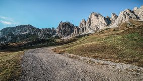 Dirt Road and Hiking Trail Track in Dolomite Italy. Dirt road and hiking trail track in Dolomites mountain, Italy, in front of Pizes de Cir Ridge mountain ranges stock photo