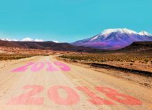 Dirt road leading into the distance to the mountain range. 2019 Happy new year concept stock image