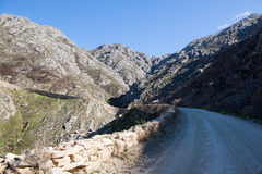 Dirt road leading over high mountain pass in daytime Stock Photography