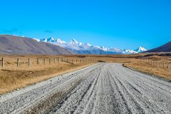 Dirt road leading to mountains in Ashburton Lakes District, South Island, New Zealand.  royalty free stock photography
