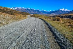 Dirt road leading to mountains in Ashburton Lakes District, South Island, New Zealand royalty free stock image