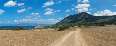 Dirt road leading to mountains. Horizontal panorama of dirt road leading through plain valley to mountains in Akamas national park, Cyprus Royalty Free Stock Photo