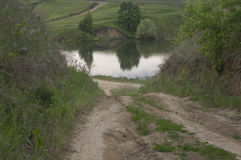 A dirt road leading to a pond. Dirt road leading to a pond Stock Photo