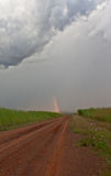 Dirt road leading to the rainbow. In the countryside of the South African highveld near Machadodorp royalty free stock photo